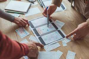 Cropped view of designers working with app sketches and template of mobile website at table